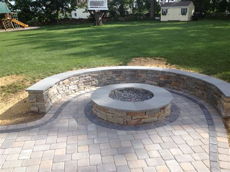 paver patio with pit sitting wall with bluestone cap surrounds a