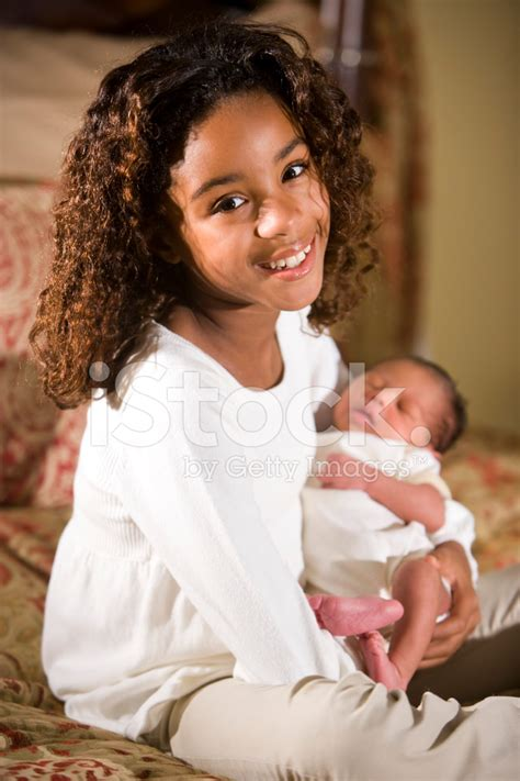 Loving Family Kids Bedroom african american child holding tiny newborn baby stock