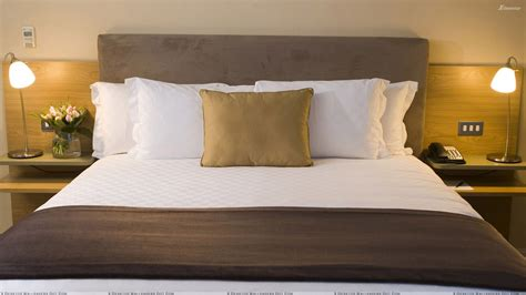 front closeup of white and brown bed side ls wallpaper