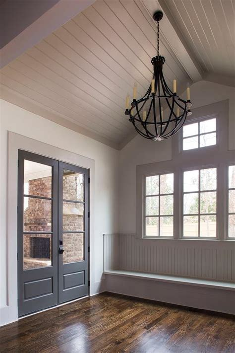 window on ceiling gray shiplap vaulted ceiling mudroom bench cottage