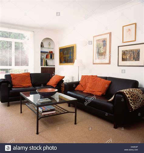 living room with black leather sofa orange cushions on black leather sofas in living room with