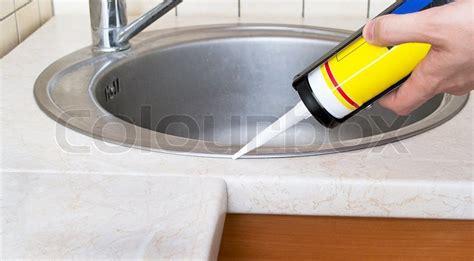 kitchen sink caulk seal plumber putting a silicone sealant to installing a kitchen
