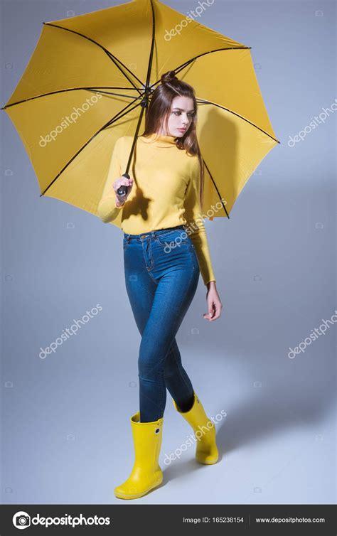 umbrella rubber st in rubber boots with umbrella stock photo