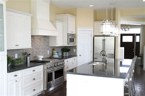 White cabinets   dark counters   stone backsplash   pale yellow walls