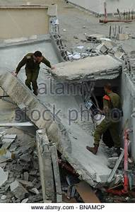 An Israeli soldier stand amid the rubble of a destroyed ...