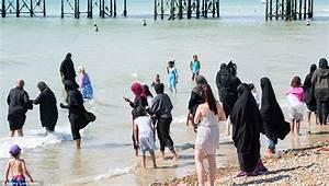 Islamic women enjoy a paddle on Brighton beach in ...