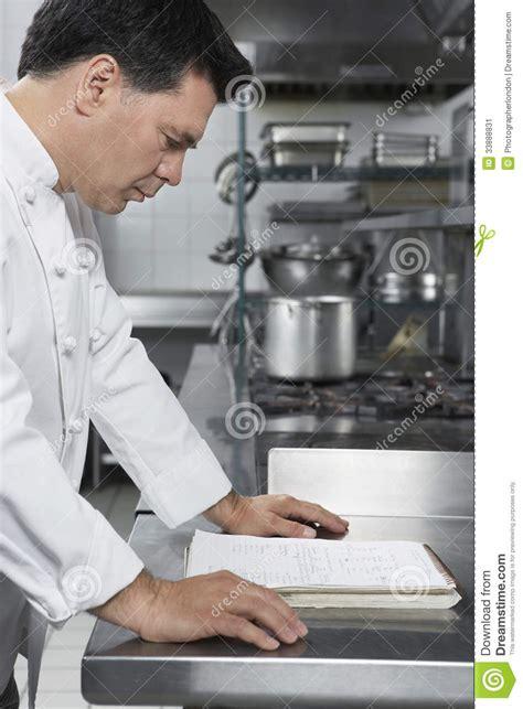 chef masculin reading recipe book dans la cuisine image stock image 33888831