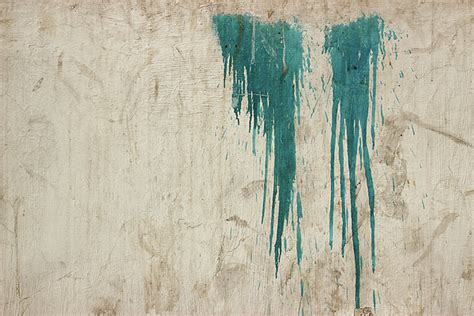 A Minimalist Photo Of Two Patches Of Dripping Blue Paint