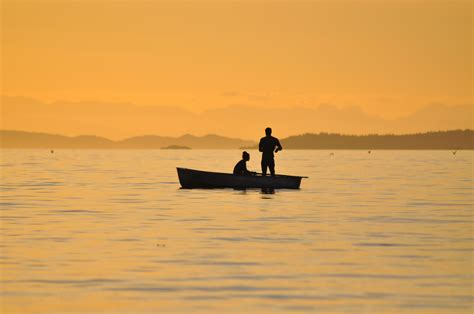 People On A Boat by 2 People Standing Sitting In A Boat On Body Of Water